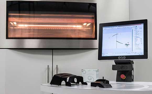 Kit para impressão das peças de reposição (impressora 3D  e computador) ao lado das primeiras peças geradas  pelo novo processo de fabricação